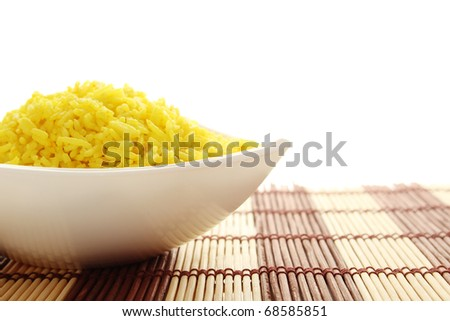 Boiled yellow rice boiled in white bowl. Plate stands on a wooden mat. Isolated on a white background