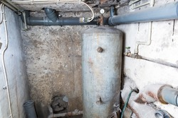 Boiler in home basement. Water tank of house. Hydraulic equipment