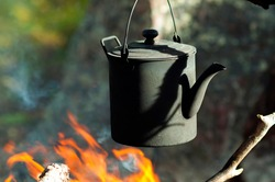 Boiling hot water with kettle on bonfire in the forest