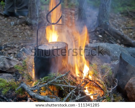 Boiling water in a kettle on fire. Set for a survival in the wood - stock photo