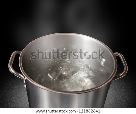 Boiling water in a kitchen pot as a symbol of cooking or food preparation and sterilization of contaminated tap water for healthy pure drinking liquid on a black background.