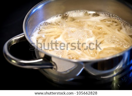Boiling water with noodles in the steel pan