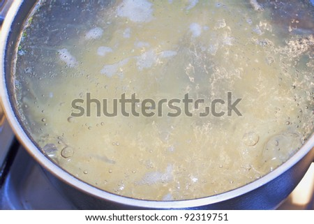 Boiling water with pasta inside a metal pot - stock photo