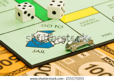 BOISE, IDAHO - NOVEMBER 18, 2012:  The car piece is speeding away from the go to jail spot on the famous Hasbro game Monopoly.