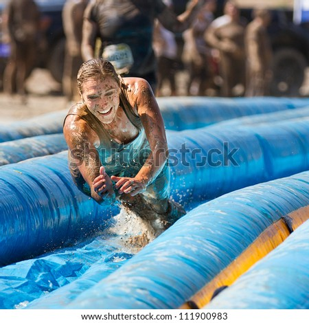 BOISE, IDAHO/USA - AUGUST 25:Unidentified woman jumps to go down the slide. The Dirty dash is a 10k run through obstacles and mud on August 25, 2012 in Boise, Idaho