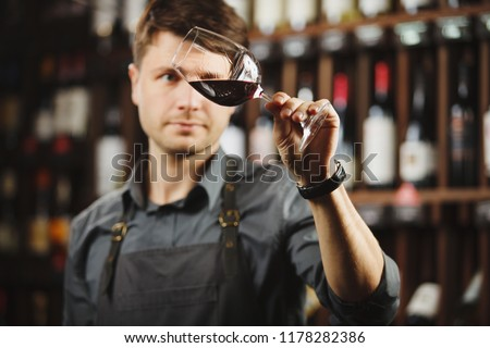 Bokal of red wine on background, male sommelier appreciating drink #1178282386