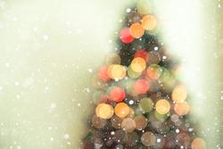 Bokeh christmas tree background with snowfall - defocused lights