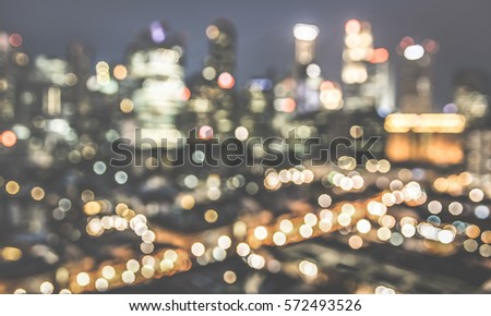 Bokeh filter of Singapore skyline from above during the blue hour - Asian modern city scape with spectacular nightscape panorama - Blurred defocused night lights on retro desaturated contrast filter #572493526