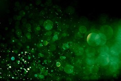 Bokeh green on a black background. Blur and bokeh abstract , vibrant colors and textured.