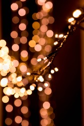 Bokeh lights background in yellow and lilac colors on black. Christmas lights string garland, festive overlay