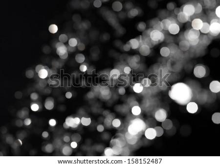 Bokeh lights on black background, shot of flying drops of water in the air, defocused water drops levitation on dark, blurred