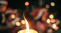 Bokeh of candle light and blurred carolers singing Christmas song in night of Christmas eve