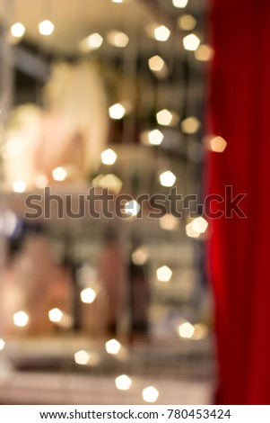 Bokeh of Christmas light garland on the red curtain. #780453424