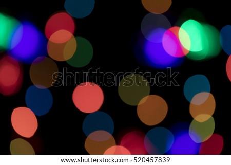 Bokeh vague colorful scattered celebration christmas lights on black background
