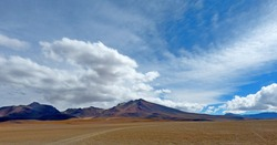 Bolivian Andes mountains in desert. Volcanic landscape. Vast extreme terrain. Impressive cloudy sky. Adventure. Road to volcano Ollague. Clouds over mountains.