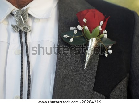 Bolo tie with classic red rose wedding boutonniere
