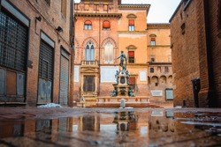 Bologna in the morning, looking Neptune statue in main square with sunlight and reflection in a puddle on the street
