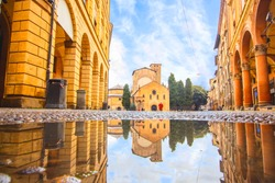 Bologna in the morning, looking Saint Stefano church in square with sunlight and reflection in a puddle on the street. Elderly granmother walking