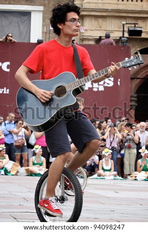 BOLOGNA, ITALY - JUN 18: Young boy on mono-cycle playing a guitar and singing a song during the 'Partòt' Street Parade 2011 in 'Piazza Maggiore' Bologna, Italy on Jun 18, 2011.