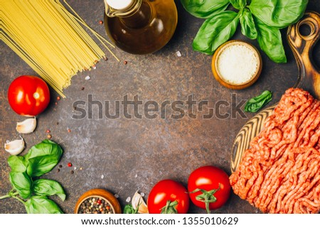 Bolognese pasta cooking concept: raw minced meat, tomatoes, pasta, parmesan, garlic, basil, olive oil on a dark background, Top view. place for text #1355010629