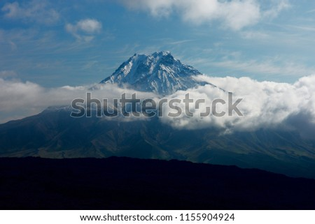 Bolshaya Udina mountain on Kamchatka peninsula, bursting through clouds covering snow line with dark lava field in front of it #1155904924