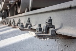 Bolted rail fastening to reinforced concrete sleepers. Connecting the rails with sleepers. Fragment of railway tracks, close-up.