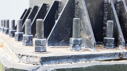 Bolts and nuts on the cement base. Several gray double bolts are firmly fixed to a steel column to a concrete base. Close focus and select an object