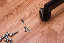 Bolts, screws and chair wheel on wooden floor