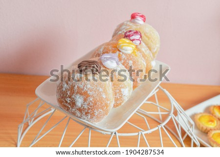 Bomboloni are irresistibly light and delicious Italian doughnuts that are fried, coated in granulated sugar, and traditionally stuffed with pastry cream Stock photo ©