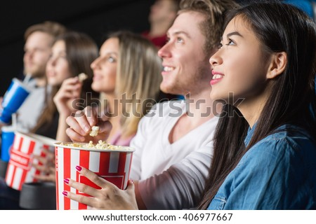 Bon appetit! Closeup shot of a young woman feeding her cheerful laughing man with popcorn at the movie theater