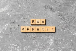 Bon Appetit word written on wood block. Bon Appetit text on cement table for your desing, concept.