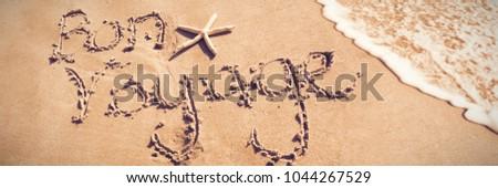 Bon voyage written on sand at beach