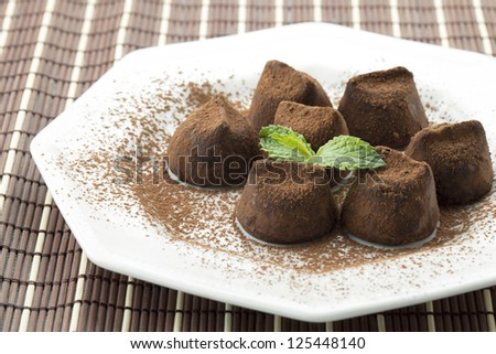 Bonbon chocolate with cocoa powder and mint leaf on a plate