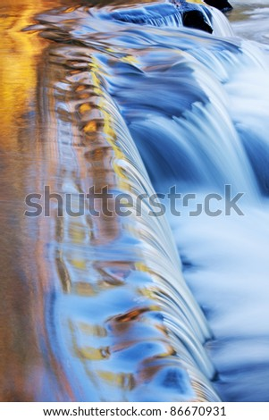 Bond Falls cascade captured with motion blur and illuminated by reflected color from sunlit autumn maples and blue sky overhead, Michigan's Upper Peninsula, USA