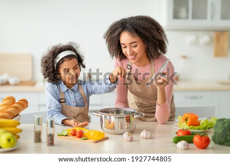 Bonding Concept. Cheerful african american mother helping her daughter to cook, teaching little girl how to prepare healthy vegetable soup, salting water in pot, cooking together at home.