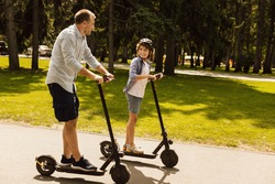 Bonding Concept. Father having ride on e-scooter with his cheerful son on the road in park, free space