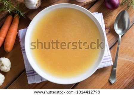 Bone broth made from chicken on a wooden table, with vegetables in the background, top view