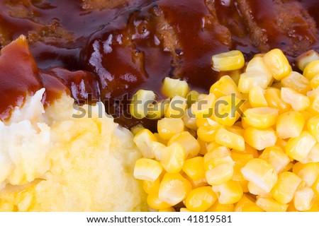 Boneless pork ribs with corn and mashed potatoes.
