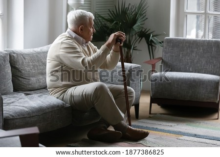 Bones ache on weather. Thoughtful mature male with grey hair resting on sofa leaning on stick feeling hard to move. Sad tired old man suffer of walking with limp need rehabilitation after leg trauma