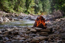 Bonfire in the mountains by the river. Rest and picnic.