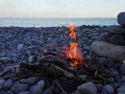 Bonfire or campfire in stone place on pebbles beach on background of sea & evening sky. Bonfire in campfire on pebble coast. Bright bonfire burning on beach at sunset. Campfire romantic background