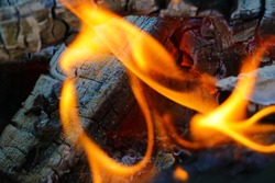 Bonfire. Orange flame of a fire. Bonfire on the grill with smoke. Arson or natural disaster. Bonfire close. Fire in nature. Bonfire background.
