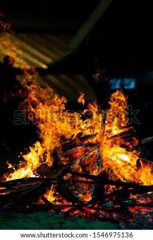 Bonfire that burns on a dark background, wood burning flame. #1546975136