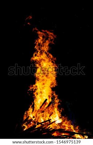 Bonfire that burns on a dark background, wood burning flame. #1546975139