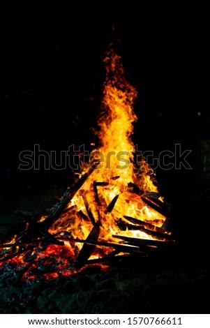 Bonfire that burns on a dark background, wood burning flame. #1570766611