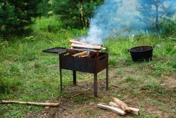 Bonfire with charred wood on a metal brazier. Burning wood in a brazier. Cooking barbecue. Burning in metal box logs firewood for barbecue outdoor on sunny day.