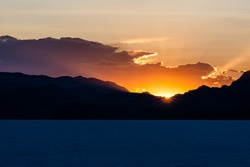 Bonneville Salt Flats dark blue landscape near Salt Lake City, Utah and silhouette mountain view and sunset sun rays glowing behind clouds