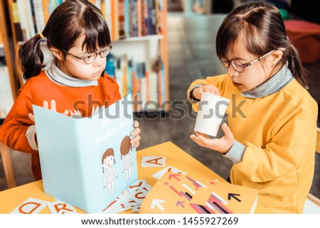 Book about self-knowledge. Interested dark-haired kids in bight outfits being involved in learning process while visiting classes