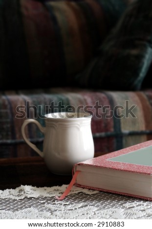 Book and coffee cup on table with lace cloth; blurred sofa in background