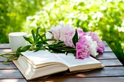 Book and cup of tea on a wooden table with flowers, summer garden, concept of relaxation and reading
